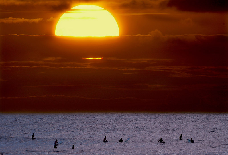 Surfers in the last bits of the light at sunset still waiting for their wave at Sunset Beach on the North Shore of Oahu, Hawaii