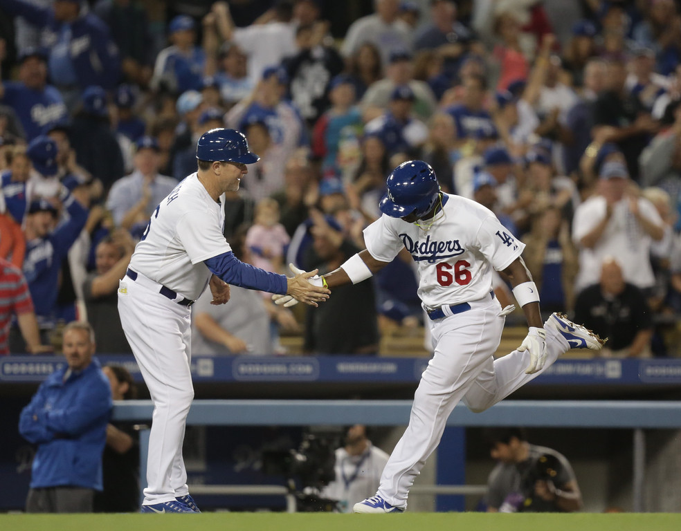 . Los Angeles Dodgers\' Yasiel Puig (66) celebrates with third base coach Tim Wallach as he rounds the bases after hitting a home run during the fifth inning of their baseball game against the San Diego Padres, Tuesday, June 4, 2013, in Los Angeles. (AP Photo/Jason Redmond)