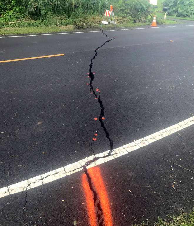 . This photo provided by Shane Turpin shows a cracked road after the eruption from Kilauea Volcano on Hawaii\'s Big Island Friday, May 4, 2018. The Kilauea volcano sent more lava into Hawaii communities Friday, a day after forcing nearly 1,500 people to flee from their mountainside homes, and authorities detected high levels of sulfur gas that could threaten the elderly and people with breathing problems. (Shane Turpin/seeLava.com via AP)