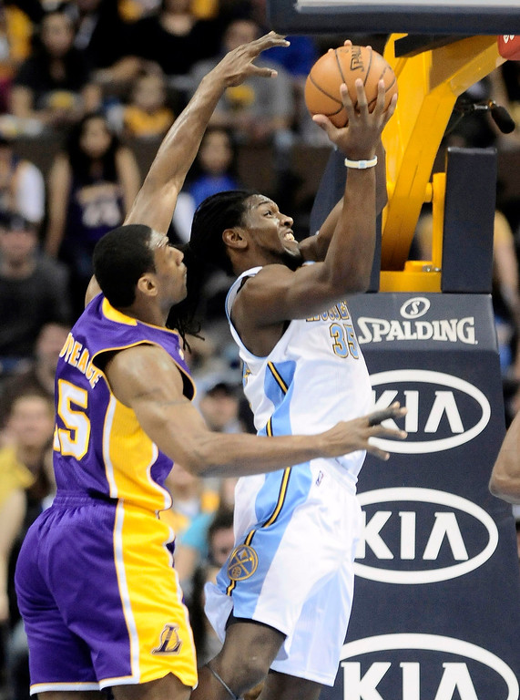 . Denver Nuggets Kenneth Faried (R) slips past Los Angles Lakers Metta World Peace (L) for a shot during their NBA basketball game in Denver, Colorado February 25, 2013. REUTERS/Mark Leffingwell