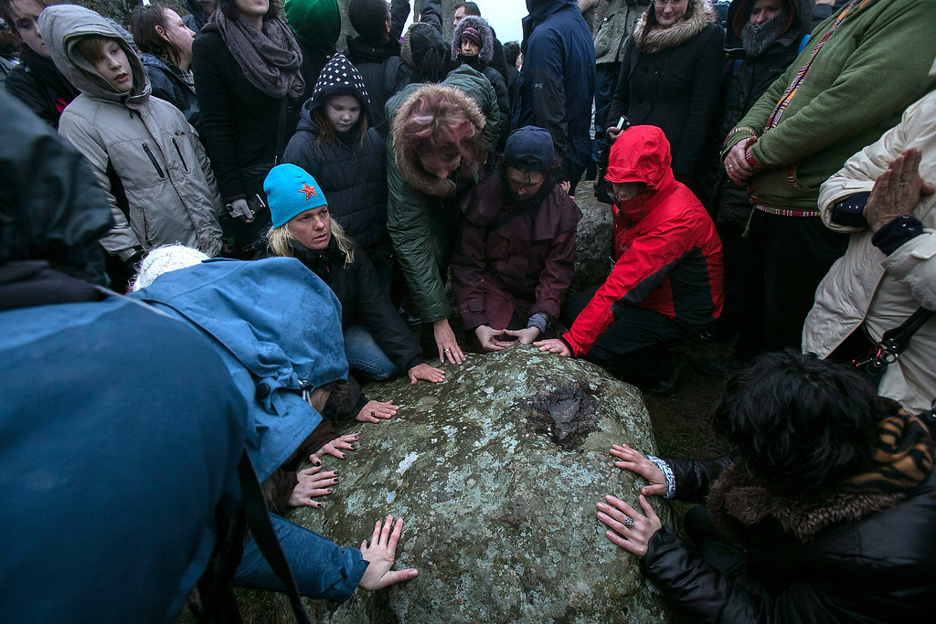 . People touch a stone inside Stonehenge as druids, pagans and revelers gather in the centre of Stonehenge, hoping to see the sun rise, as they take part in a winter solstice ceremony at Stonehenge on December 21, 2013 in Wiltshire, England.  (Photo by Matt Cardy/Getty Images)
