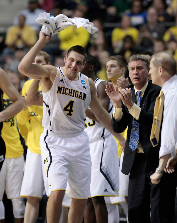 . Michigan Wolverines\' Mitch McGary (C) celebrates on the bench as they play the South Dakota State Jackrabbits during the second half of their second round NCAA tournament basketball game in Auburn Hills, Michigan March 21, 2013.  REUTERS/ Jeff Kowalsky