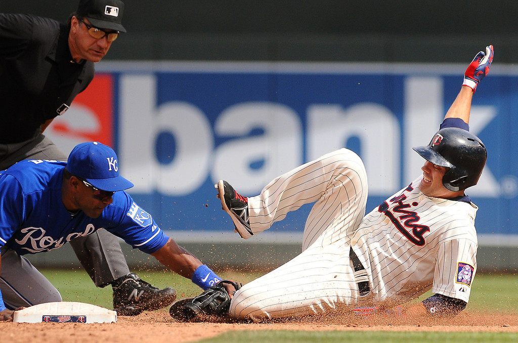 . Minnesota third baseman Jamey Carroll (8) is tagged out by Kansas City shortstop Miguel Tejada  as he tries to turn a single into a double during the third inning. Watching the play is umpire Phil Cuzzi. (Pioneer Press: John Autey)