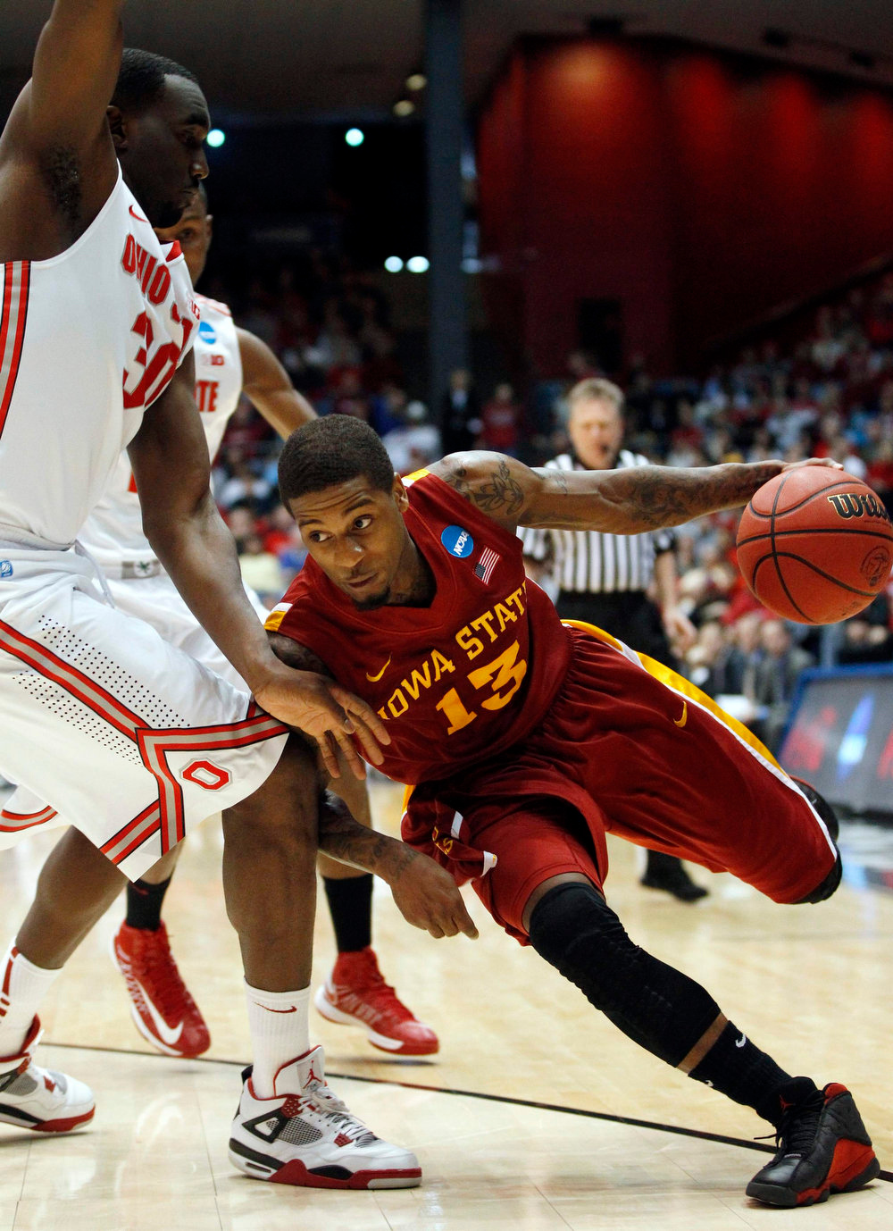 . Iowa State Cyclones guard Korie Lucious (R) dribbles past Ohio State Buckeyes forward Evan Ravenel (30) during the first half of their third round NCAA tournament basketball game in Dayton, Ohio March 24, 2013.   REUTERS/Matt Sullivan