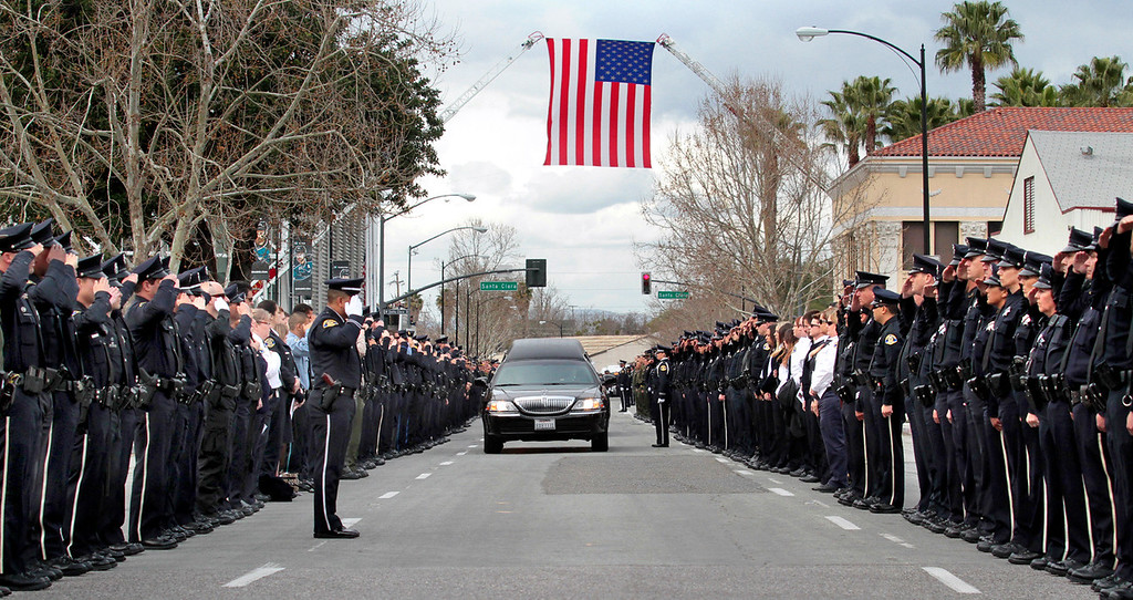 . Police officers from around the state line South Autumn Street outside HP Pavilion in San Jose to salute the hearses carrying fallen Santa Cruz police detective Elizabeth Butler and detective Sgt. Loran \'Butch\' Baker after Thursday�s memorial. (Shmuel Thaler/Sentinel)