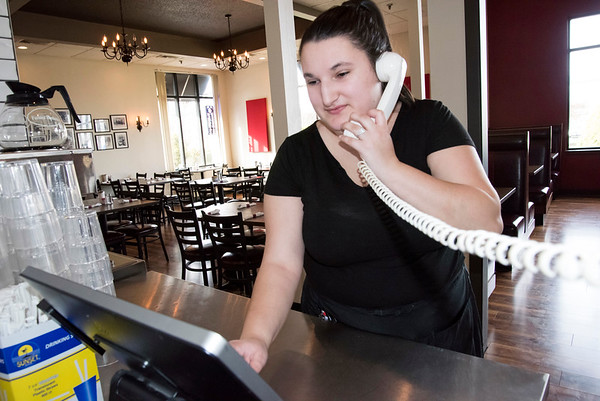 03/27/20 Wesley Bunnell | StaffrrJenna Martino enters a to go phone order inside of an empty Bell City Diner on Monday afternoon. Health officials shut down all state restaurants at 8p.m. to dining inside while still allowing them to offer deliver and offer to go service.