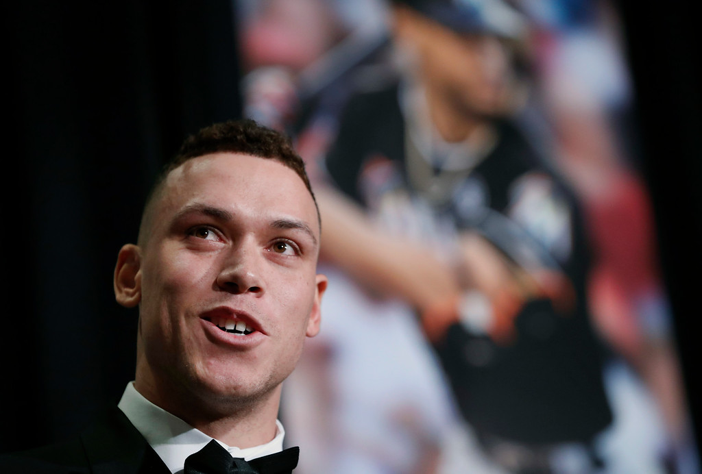 . American League Rookie of the Year Aaron Judge speaks with a photograph of his new teammate, National League Most Valuable Player Giancarlo Stanton, behind him after accepting his award during the New York Chapter of the Baseball Writers\' Association of America annual dinner in New York, Sunday, Jan. 28, 2018. (AP Photo/Kathy Willens)