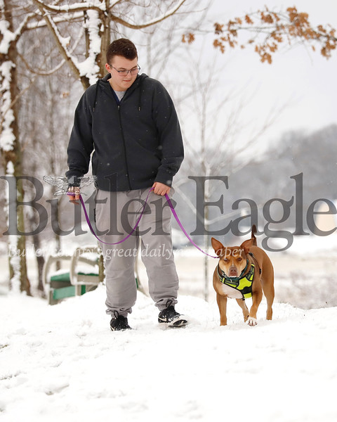Butler County Humane Society kennel assistant Tyler Boyer takes Quinn, a 2 1/2-year-old husky pitbull mix for a walk Wednesday. Seb Foltz/Butler Eagle