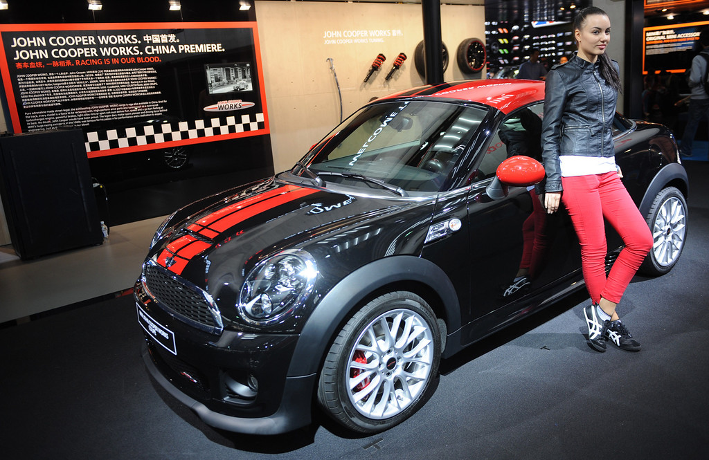 . This photo taken on April 20, 2013 shows a model posing next to a Mini Cooper on media day at the Shanghai auto show. The Shanghai auto show, which opens to the public on April 21, is expected to attract more than 800,000 visitors over the course of nine days.    PETER PARKS/AFP/Getty Images