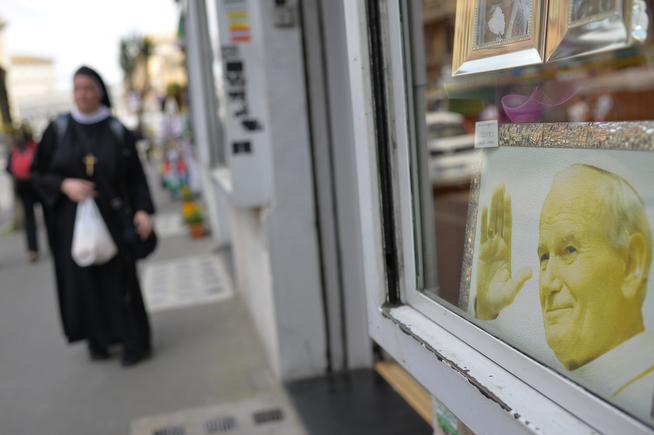 . A nun walks past a portrait of Pope John Paul II displayed in a shop window near St Peter\'s square on April 26, 2014 in Rome a day before the canonisation of Popes John XXIII and John Paul II. Popes John Paul II and John XXIII will join the roster of saints at a historic Vatican ceremony on Sunday seen as an attempt to unite conservatives and reformists, with some 800,000 pilgrims expected in Rome. The double canonisation of two of modern-day Catholicism\'s most influential figures will be presided over by Pope Francis and may be attended by his elderly predecessor Benedict XVI, bringing two living pontiffs together to celebrate two deceased predecessors. (ANDREAS SOLARO/AFP/Getty Images)