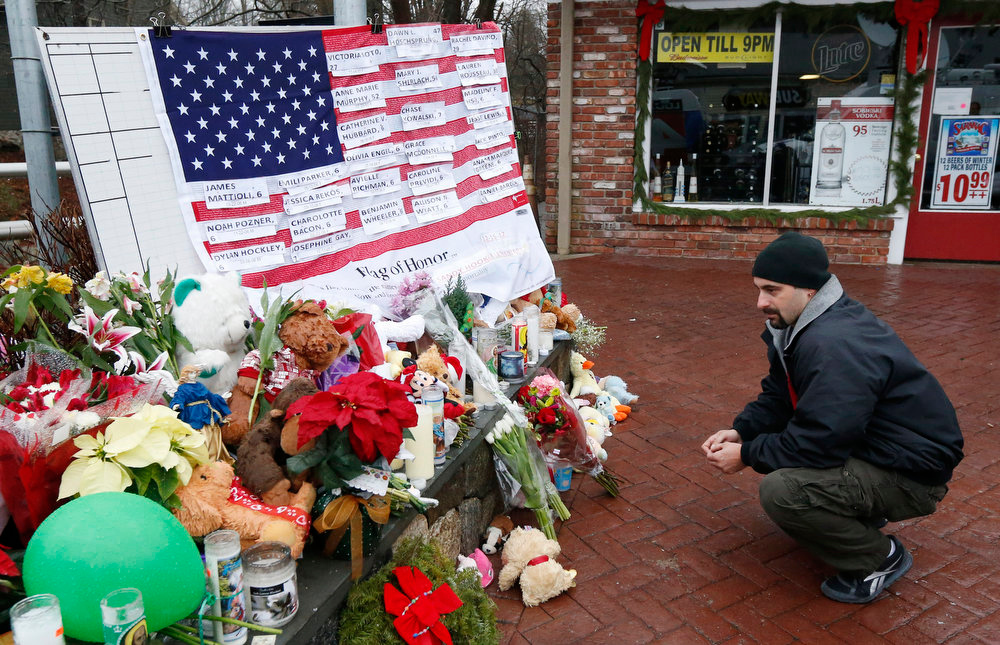 Description of . Mark Sorrentino, of Naugatuck, Conn., pays respects near a U.S. flag donning the names of victims on a makeshift memorial in the Sandy Hook village of Newtown, Conn., as the town mourns victims killed in a school shooting, Monday, Dec. 17, 2012. Authorities say a gunman killed his mother at their home and then opened fire inside the Sandy Hook Elementary School in Newtown, killing 26 people, including 20 children, before taking his own life, on Friday. (AP Photo/Julio Cortez)