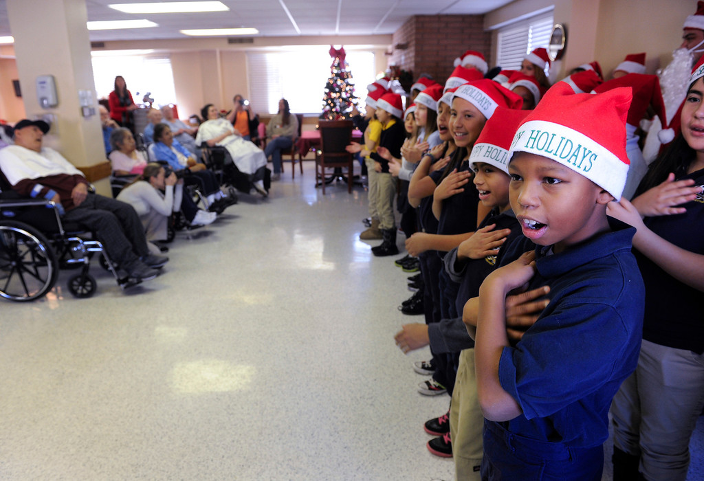 . Soul Liptrot, 10, right, and his fellow students and parents from the Denver Center for International Studies at Ford Elementary School spend a Saturday singing holiday songs in three different languages to the residents of the Kindred Care nursing home. (Photo by Kathryn Scott Osler/The Denver Post)
