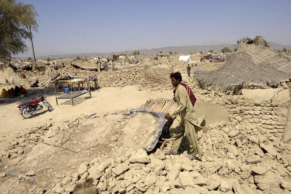 . A Pakistani survivor walks through the debris of destroyed houses in the earthquake-devastated district of Awaran on September 25, 2013.   AFP PHOTO/Banaras KHAN/AFP/Getty Images