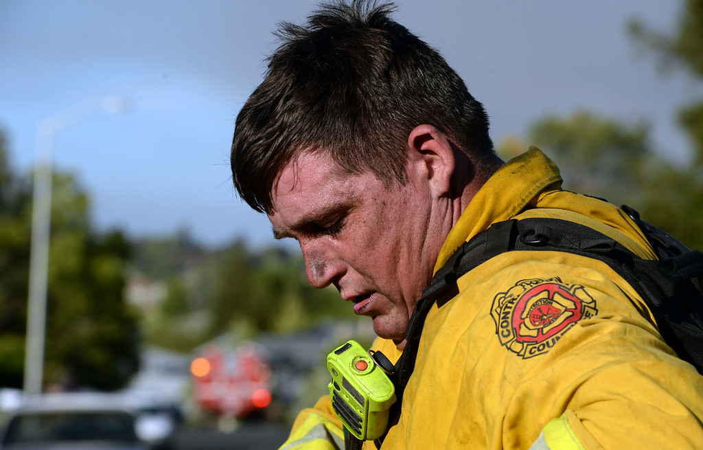 . Contra Costa County firefighter Whit MacDonald looks down to attach equipment to his suit after getting water from a neighbor along Foothill Drive in Antioch, Calif., on Wednesday, June 24, 2015. (Susan Tripp Pollard/Bay Area News Group)