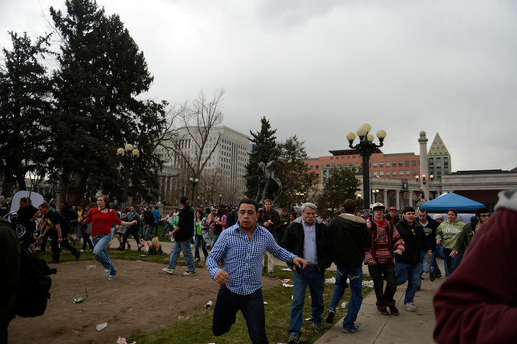 . DENVER, CO. - APRIL 20: April 20: The crowd runs away from the gun shots at Civic Center Park in Denver Colorado, Saturday April 20th, 2013 after the 4/20 pot rally. Two people were shot during Saturday\'s annual 4/20 marijuana rally, held on a day cannabis enthusiasts regard as a holiday called 4/20 that drew tens of thousands to Denver\'s Civic Center park. This is the first 4/20 marijuana rally since Colorado voters legalized marijuana use for people 21 and older in November. April 20, 2013 Denver, Colorado. (Photo By Joe Amon/The Denver Post)