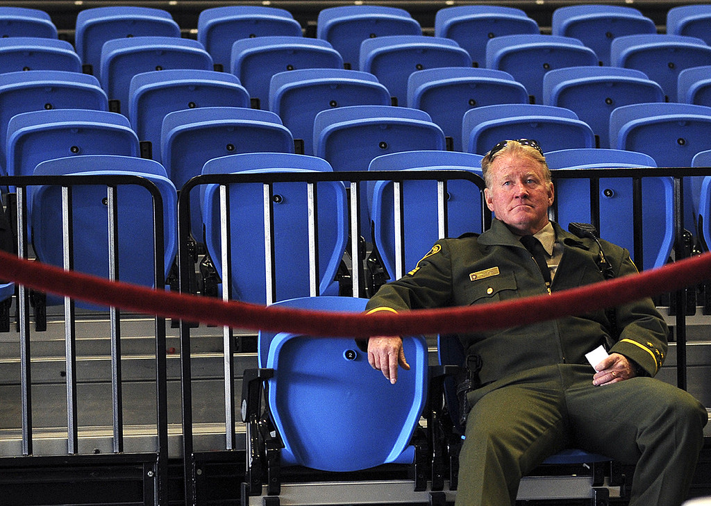 . Sherriff Sergeant Joe Clark watches the live broadcast of the memorial service for detectives Sgt. Loran \'Butch\' Baker and Elizabeth Butler Thursday at Kaiser Permanente Arena in Santa Cruz (Matthew Hintz/Sentinel).