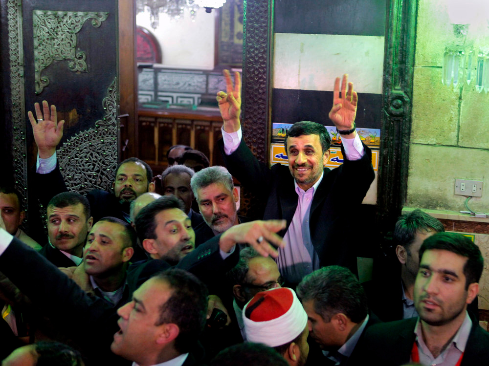 Description of . Iran's President Mahmoud Ahmadinejad, center, waves to Egyptian worshippers after he visits the shrine of Imam Hussein, the grandson of Islam's Prophet Mohammad, in Cairo, Egypt, Tuesday, Feb. 5, 2013. Egypt's most prominent Muslim cleric, the sheik of Al-Azhar, has warned Iranian President Mahmoud Ahmadinejad against interfering in Arab Gulf countries or trying to spread Shiite influence. Ahmadinejad, on a landmark visit to Egypt on Tuesday, received an uneasy reception from Ahmed el-Tayeb at Al-Azhar, the Sunni Muslim world's foremost Islamic institution.(AP Photo/Amr Nabil)