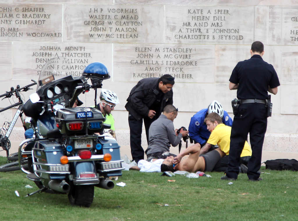 . Denver, CO. - April 20: Denver Paramedics, Denver Police officers and a bystander attend to a shooting victim at Civic Center Park in Denver Colorado, Saturday April 20th, 2013 after a 4/20 pot rally. Two people were shot during Saturday\'s annual 4/20 marijuana rally, held on a day cannabis enthusiasts regard as a holiday called 4/20 drew tens of thousands to Denver\'s Civic Center park. This is the first 4/20 marijuana rally since Colorado voters legalized marijuana use for people 21 and older in November. (Photo By Alex Scott/Special to The Denver Post)