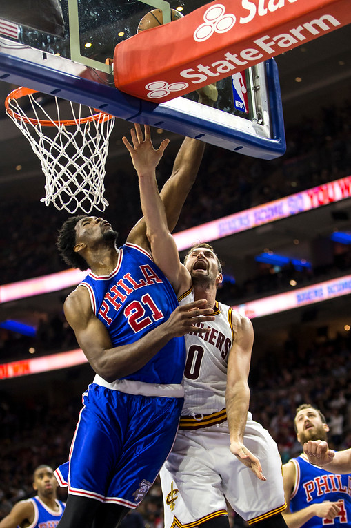 . Philadelphia 76ers\' Joel Embiid, left, blocks the shot and collides with Cleveland Cavaliers\' Kevin Love, right, during the first half of an NBA basketball game, Saturday, Nov. 5, 2016, in Philadelphia. (AP Photo/Chris Szagola)