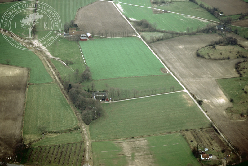Farmland west of Ravlunda church - with plantations, buildings and prehistoric remains (Lingers kulle) (2 April, 1989). | LH.0481