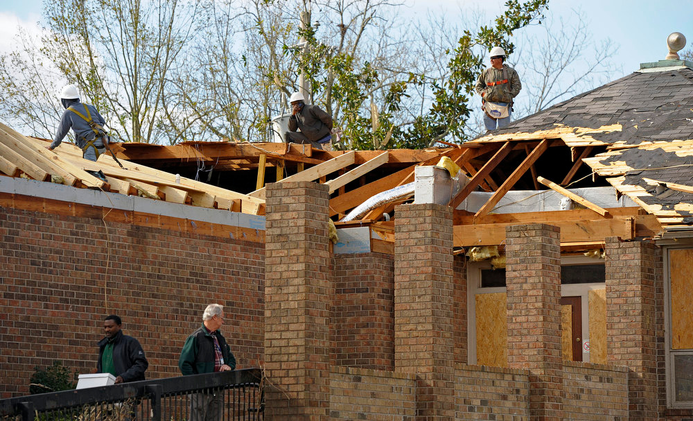 . Repair crews try to cover the damaged roof of a business near Mobile Infirmary as residents clean up and assess the damage from a Christmas Day tornado Wednesday, Dec. 26, 2012 in Mobile, Ala. With only a handful of injuries and no deaths reported statewide from the storms, the head of the state\'s emergency response said it was difficult to fathom how the toll wasn\'t worse. (AP Photo/G.M. Andrews)