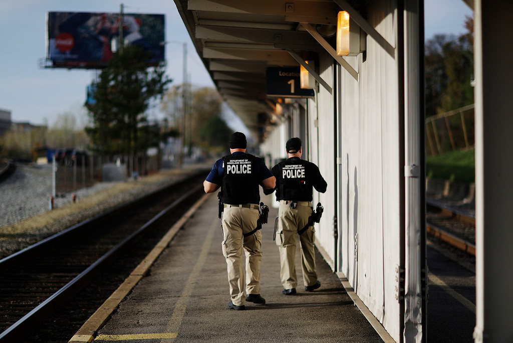 . Department of Homeland Security officials patrol along a platform while waiting for a train to New Orleans to arrive in Atlanta, Wednesday, Nov. 23, 2016. Almost 49 million people are expected to travel 50 miles or more for the Thanksgiving holiday, the most since 2007, according to AAA. (AP Photo/David Goldman)