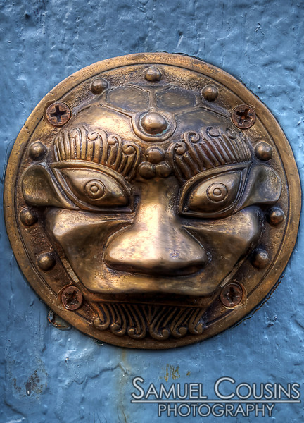 A brass face decoration on the door of a workshop.