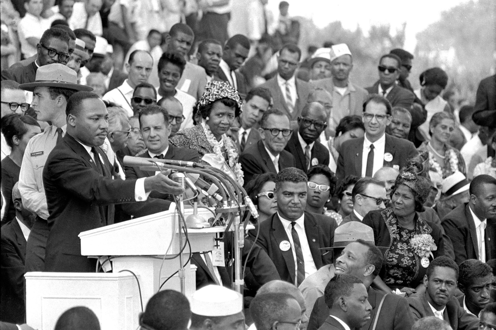 Description of . In this Aug. 28, 1963 file photo, the Rev. Dr. Martin Luther King Jr., head of the Southern Christian Leadership Conference, speaks to thousands during his