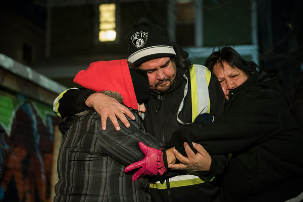 DAVID LIPNOWSKI / WINNIPEG FREE PRESS  (L-R) Aunt and Uncle of Tyler Smoke, Cheryl Paul, Orville Smoke, and Aunt Cheryl Beaulieu  console each other at the vigil for Tyler Smoke in the back alley of Victor Street where he was murdered on Christmas Day, held Thursday December 27, 2018.