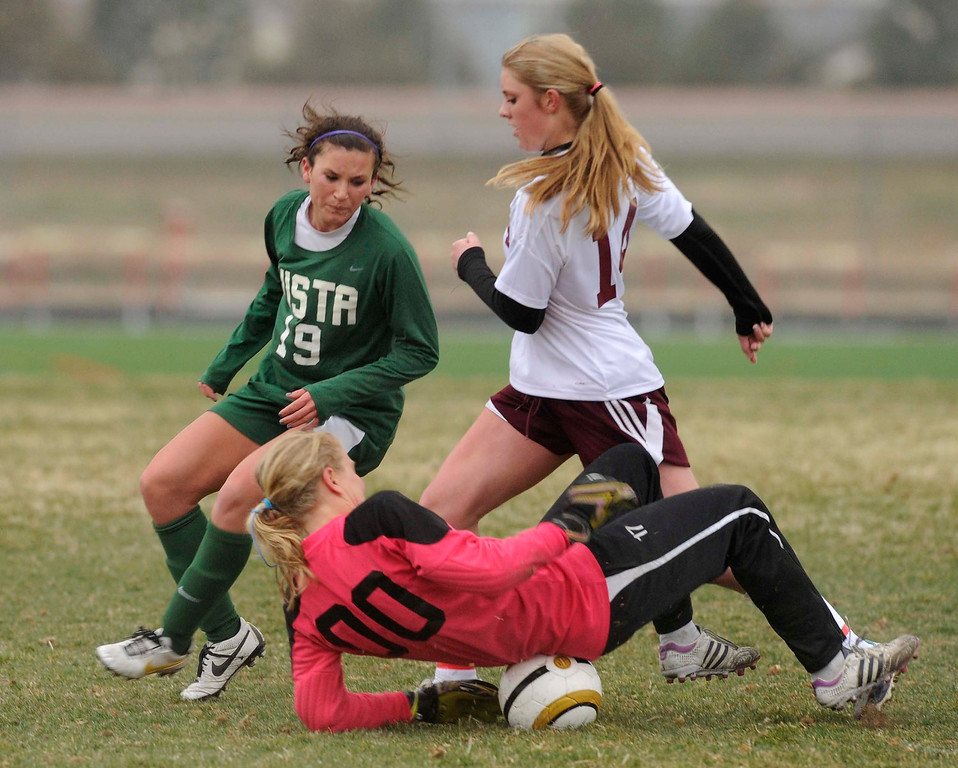 . Mustangs goaltender Abigail Eustace smothered the ball as Golden Eagle forward Kelsey Luke (19) rushed the net in the first half. The Mountain Vista High School girl\'s soccer team defeated Ponderosa 6-0 Tuesday night, April 2, 2013.  Photo By Karl Gehring/The Denver Post)