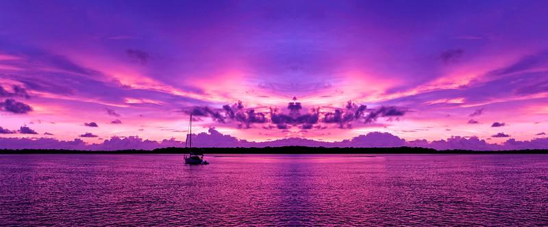 A bright  pink magenta coloured cloudy nautical coastal sunrise seascape in a purple sky. Queensland, Australia.
