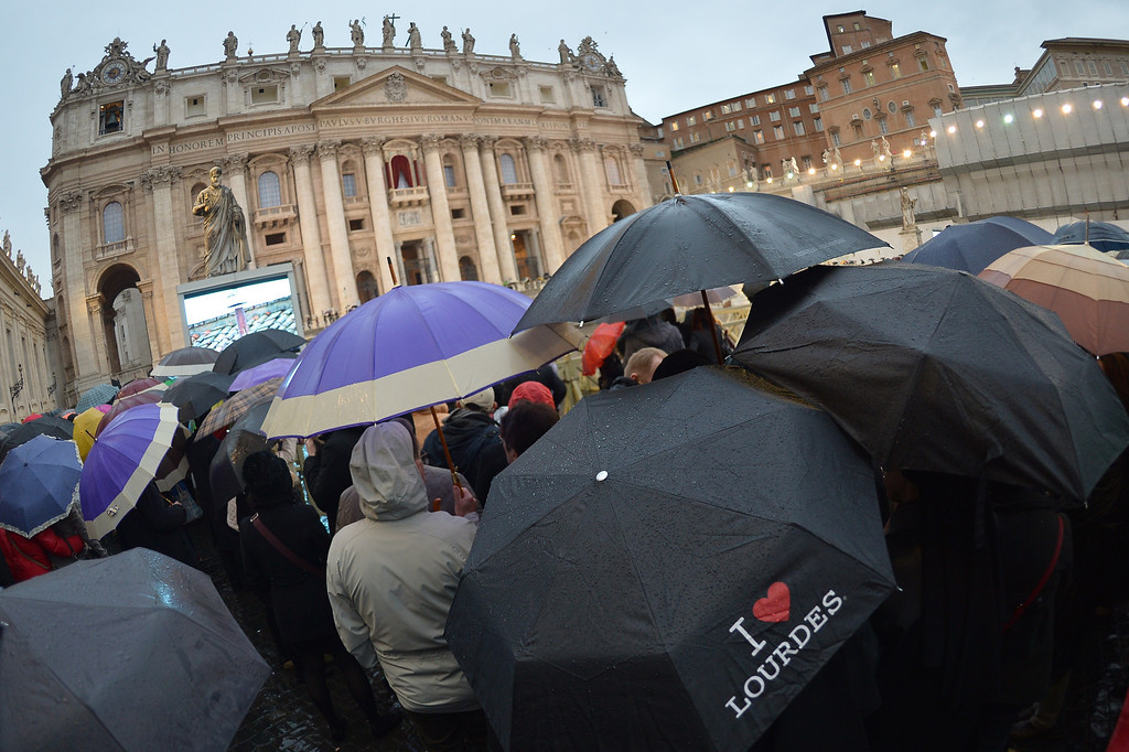. Faithfuls wait under rain for the smoke announcing the result on the second day of the papal election conclave on March 13, 2013 at St Peter\'s square at the Vatican. In a rain-swept St Peter\'s Square, tens of thousands of people were hoping today to see the puff of smoke that would signal that cardinals meeting inside the chapel had reached a decision on who should be the next pope. Despite two puffs of black smoke in as many days, signaling that the 115 cardinals in the secret conclave had yet to choose a successor to Benedict XVI, many in the crowd were optimistic.       AFP PHOTO / GABRIEL BOUYS/AFP/Getty Images