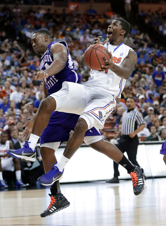 . Florida\'s Kenny Boynton, right, loses his balance as he fouled by Northwestern State\'s Gary Roberson during the second half of a second-round game of the NCAA men\'s college basketball tournament Friday, March 22, 2013, in Austin, Texas. Florida beat Northwestern State 79-47. (AP Photo/Eric Gay)