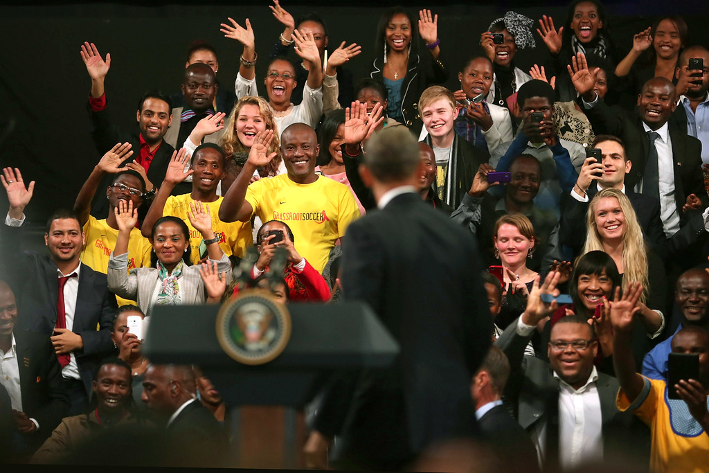 """. JOHANNESBURG, SOUTH AFRICA - JUNE 29:  Young people cheer and wave as U.S. President Barack Obama arrives for a \""""town hall\"""" meeting with the young African leaders at the University of Johannesburg in Soweto June 29, 2013 in Johannesburg, South Africa. South Africa is the second leg of Obama\'s three-country tour of the African continent, which includes Senegal and Tanzania.  (Photo by Chip Somodevilla/Getty Images)"""