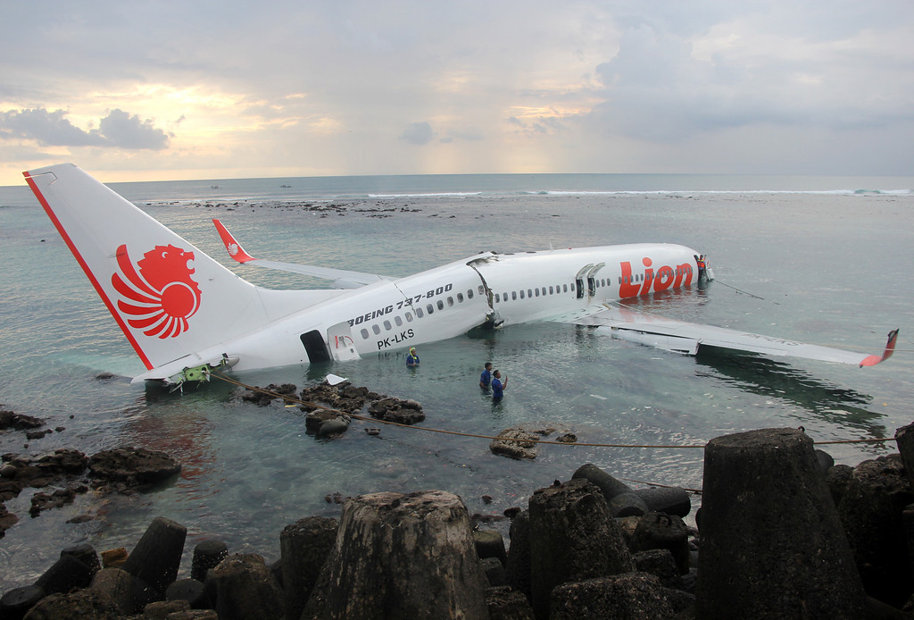 . This handout photo released by the Indonesian Police on April 13, 2013 shows a Lion Air Boeing 737 submerged in the water after skidding off the runaway during landing at Bali\'s international airport near Denpasar. An Indonesian plane carrying more than 100 passengers broke in two after missing the runway at Bali airport on April 13 and landing in the sea, leaving dozens injured but no fatalities. AFP PHOTO / Indonesian Police