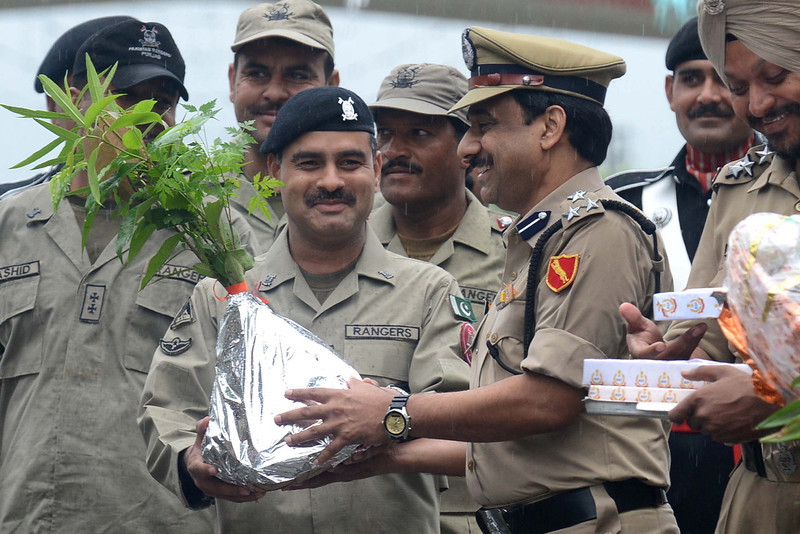 """. Indian Border Security Force (BSF) Deputy Inspector General M.F. Farooqui (3rd R) presents plants to Pakistani Ranger Wing Commander Adnan (2nd L) during a flag hoisting ceremony to celebrate India\'s Independence Day at the India-Pakistan Wagah border post on August 15, 2013. Premier Manmohan Singh warned Pakistan August 15 against using its soil for \""""anti-India activity\"""", following a fresh escalation of tensions between the nuclear-armed neighbours over a deadly attack on Indian soldiers. NARINDER NANU/AFP/Getty Images"""