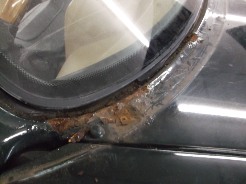 Stainless steel windscreen trim removed - Note flaking rust in lower corner