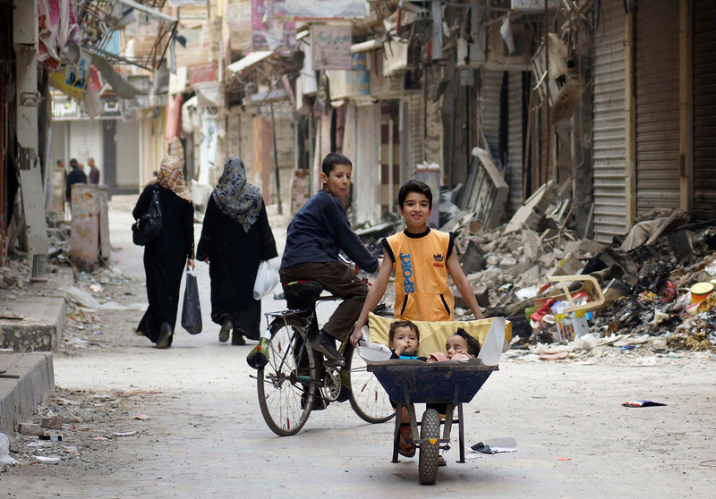 . A boy pushes a cart carrying his brothers along a street a in Deir al-Zor April 20, 2013. Picture taken April 20, 2013. REUTERS/Khalil Ashawi