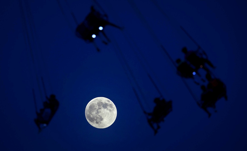 ". People ride the Luna Park Swing Ride as a ""super moon\"" rises over Coney Island on June 22, 2013. The largest full moon of the year called a \""super moon\"" will light up the night sky this weekend.   REUTERS/Carlo Allegri"