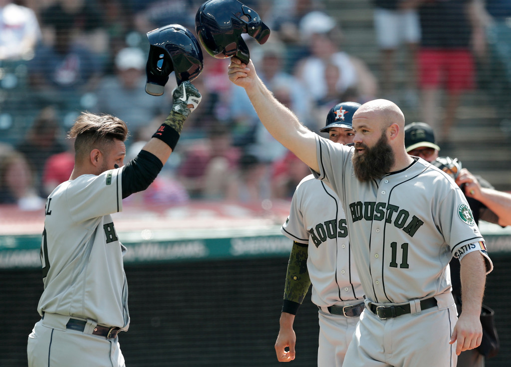 . Houston Astros\' Evan Gattis, right, is congratulated by Yuli Gurriel after hitting a three-run home run off Cleveland Indians relief pitcher Ben Taylor in the eighth inning of a baseball game, Sunday, May 27, 2018, in Cleveland. (AP Photo/Tony Dejak)