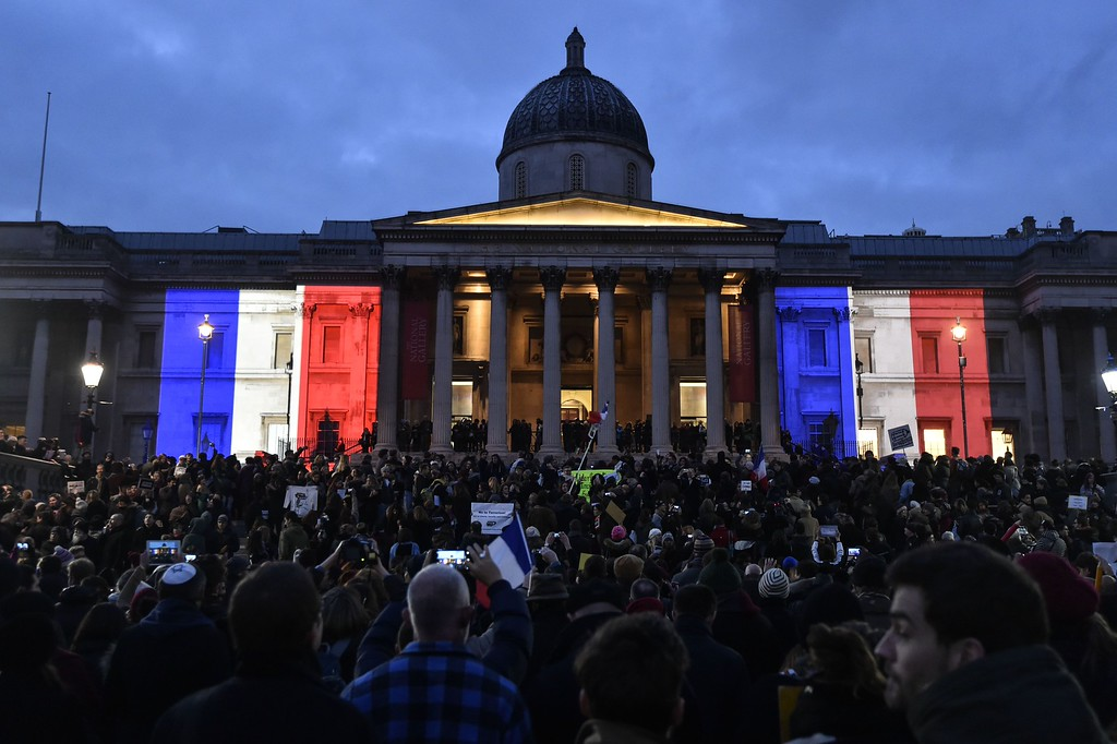 ". The National Gallery is lit up in the colours of the French flag as crowds gather in Trafalgar Square in central London on January 11, 2015 to commemorate the victims of the attacks in France that killed 17 people and injured scores more. Around 2,000 people gathered in London to honour the victims of Islamist attacks in Paris, many raising pencils to the sky in memory of those killed at satirical weekly Charlie Hebdo. Some in the crowd at Trafalgar Square carried placards saying ""Je suis Charlie\"" and waved French flags.  AFP PHOTO / NIKLAS HALLE\'NNIKLAS HALLE\'N/AFP/Getty Images"