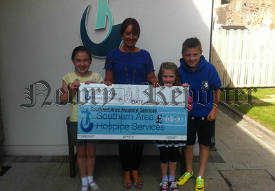 Rachel, Grace and Gerard Malley from Newry are pictured presenting a cheque for £20 to Fiona Kieran of Southern Area Hospice Services. The siblings raised the money by making and selling loom band bracelets amongst their family and friends during their summer school holidays. R1436120