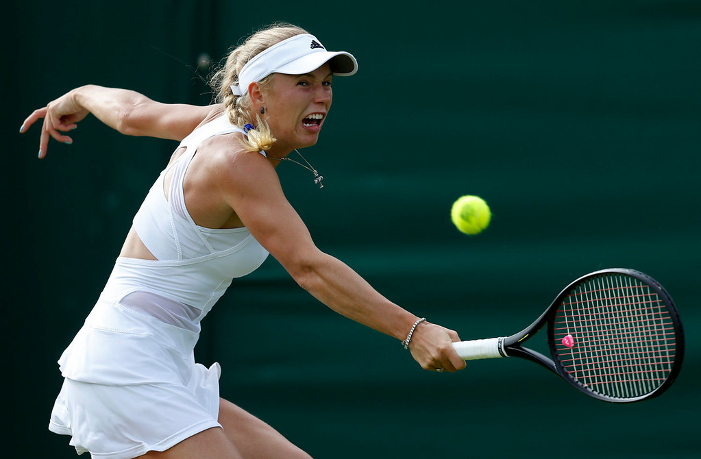 . Caroline Wozniacki of Denmark returns the ball to Estrella Cabeza Candela of Spain during their Women\'s first round singles match at the All England Lawn Tennis Championships in Wimbledon, London, Monday, June 24, 2013.  (AP Photo/Sang Tan)