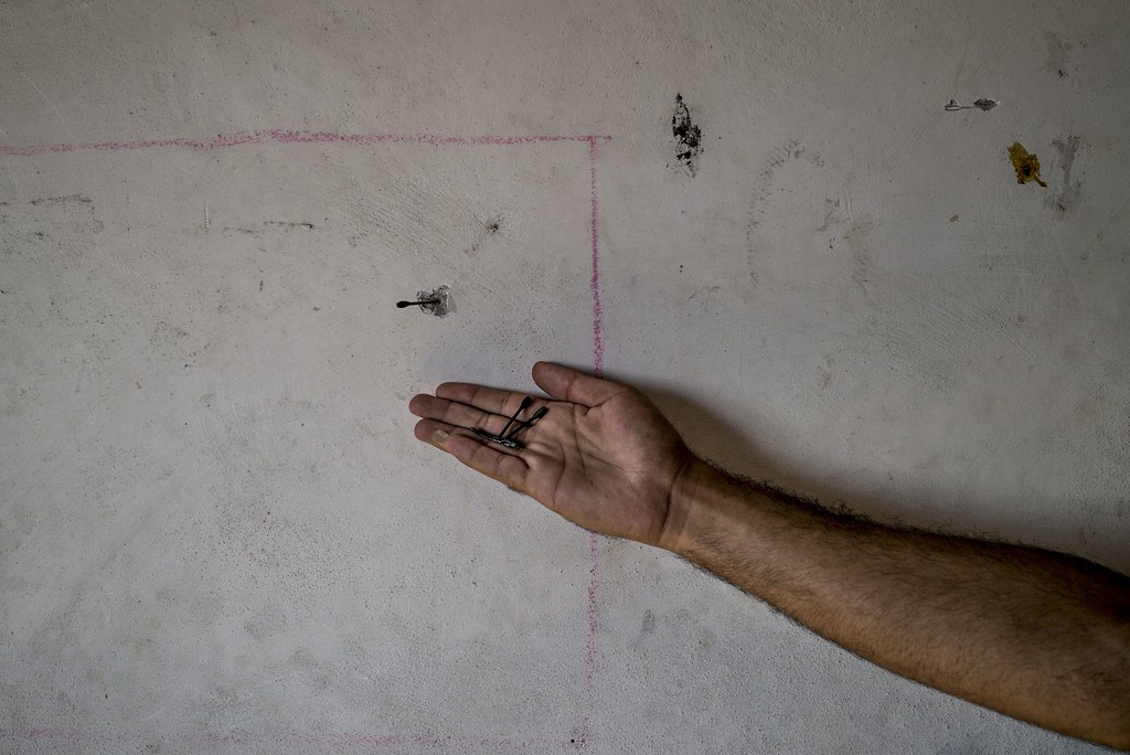 . A Palestinian man from Gaza Strip\'s central Bureij refugee camp holds in the palm of his hand some flechettes, as one is seen stuck in the wall of his house, while he inspects it on August 1, 2014. Israel declared an end to a three-day Gaza truce only hours after it began today, saying it fears a soldier was captured, jeopardising international efforts for a durable ceasefire. AFP PHOTO/MARCO LONGARI/AFP/Getty Images