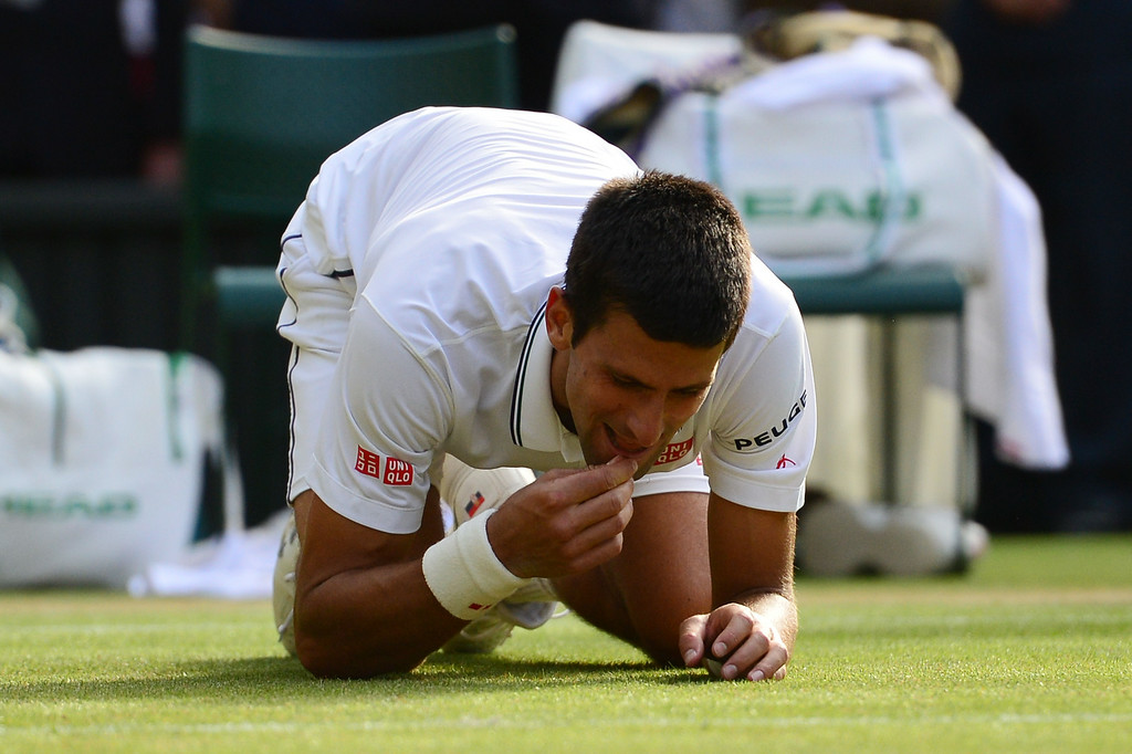 . Serbia\'s Novak Djokovic eats the grass as he celebrates winning his men\'s singles final match against Switzerland\'s Roger Federer on day thirteen of  the 2014 Wimbledon Championships at The All England Tennis Club in Wimbledon, southwest London, on July 6, 2014.    CARL COURT/AFP/Getty Images