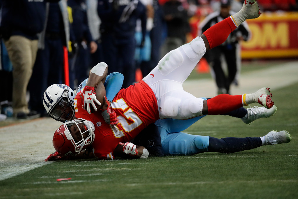 . Kansas City Chiefs running back Kareem Hunt (27) is tackled by Tennessee Titans safety Kevin Byard (31) during the first half of an NFL wild-card playoff football game, in Kansas City, Mo., Saturday, Jan. 6, 2018. (AP Photo/Charlie Riedel)