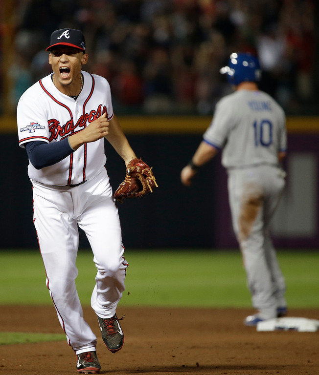 . Atlanta Braves shortstop Andrelton Simmons, left, reacts after he turned a double play against the Los Angeles Dodgers in the seventh inning during Game 2 of the National League division series on Friday, Oct. 4, 2013, in Atlanta. (AP Photo/John Bazemore)