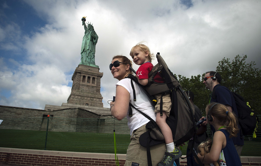 . NEW YORK, NY - JULY 4: A family walks by the Statue of Liberty on the first day it is open to the public after Hurricane Sandy on July 4, 2013 on the Liberty Island in New York City. The statue was mostly spared by the storm, but the surrounding infrastructure was badly damaged. (Photo by Kena Betancur/Getty Images)
