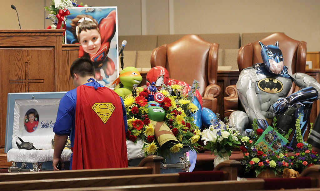 . Dale Hall, dressed as Superman, stands before the casket during a superhero-themed funeral service for his brother, Jacob Hall at Oakdale Baptist Church on Wednesday, Oct. 5, 2016, in Townville, S.C.  A 14-year-old boy killed his own father, then drove to Townville Elementary and fired on two children and a teacher as recess began.  Jacob died Saturday. (Ken Ruinard/The Independent-Mail via AP, Pool)
