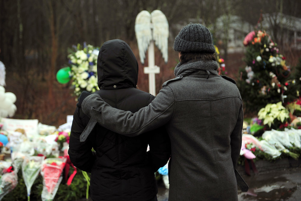 Description of . People pay their respects at a makeshift shrine to the victims of an elementary school shooting in Newtown, Connecticut, December 17, 2012. Funerals began Monday in the little Connecticut town of Newtown after the school massacre that took the lives of 20 small children and six staff, triggering new momentum for a change to America's gun culture. The first burials, held under raw, wet skies, were for two six-year-old boys who were among those shot in Sandy Hook Elementary School. On Tuesday, the first of the girls, also aged six, was due to be laid to rest. There were no Monday classes at all across Newtown, and the blood-soaked elementary school was to remain a closed crime scene indefinitely, authorities said. AFP PHOTO/Emmanuel  DUNAND/AFP/Getty Images